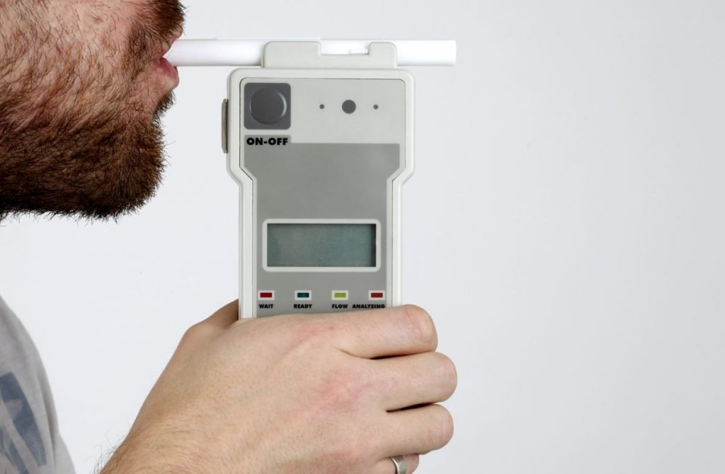 Man blowing breathalzyer breath test