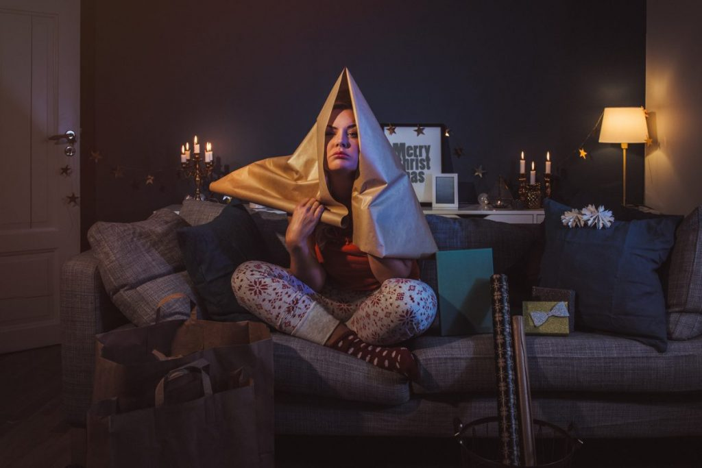 girl sitting on the couch with wrapping paper over her head