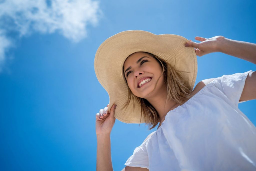 Woman with wide-brimmed hat sunny day
