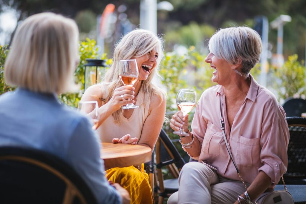 Three senior women drinking wine