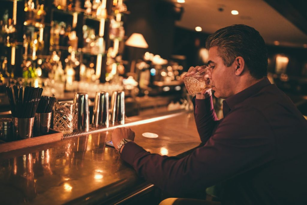 Man drinking liquor at bar
