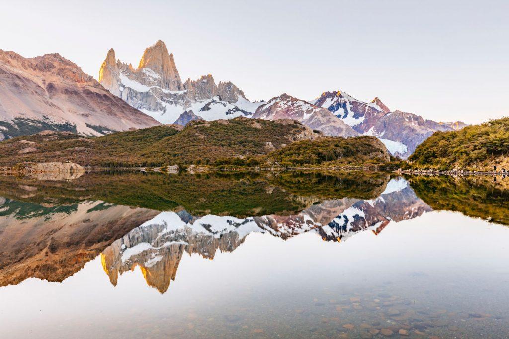 A view of Mount Fitz Roy reflected in a mirror calm Laguna Capri in Los Glaciares National Park above El Chalten