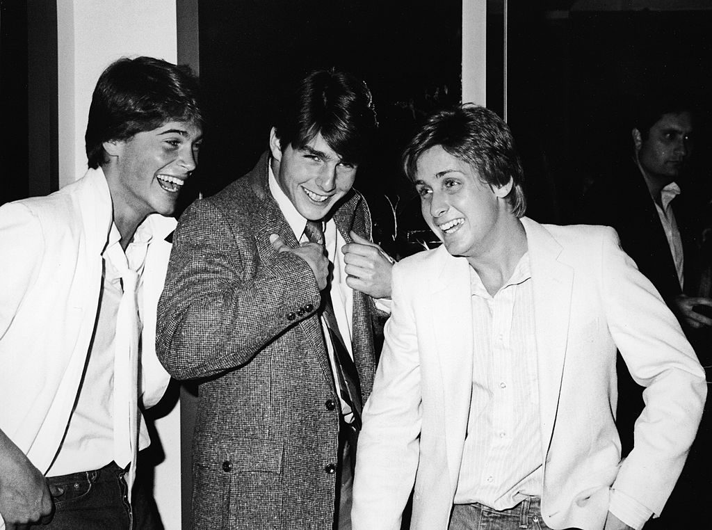 American actors Rob Lowe, Tom Cruise, and Emilio Estevez at the premiere screening of the TV movie, 'In The Custody of Strangers,' directed by Robert Greenwald, Beverly Hills, California, April 22, 1982. Lowe and Estevez both wear white jackets with open-neck shirts and Cruise wears a darker jacket; Lowe and Cruise also wear ties and have upturned collars on their jackets.