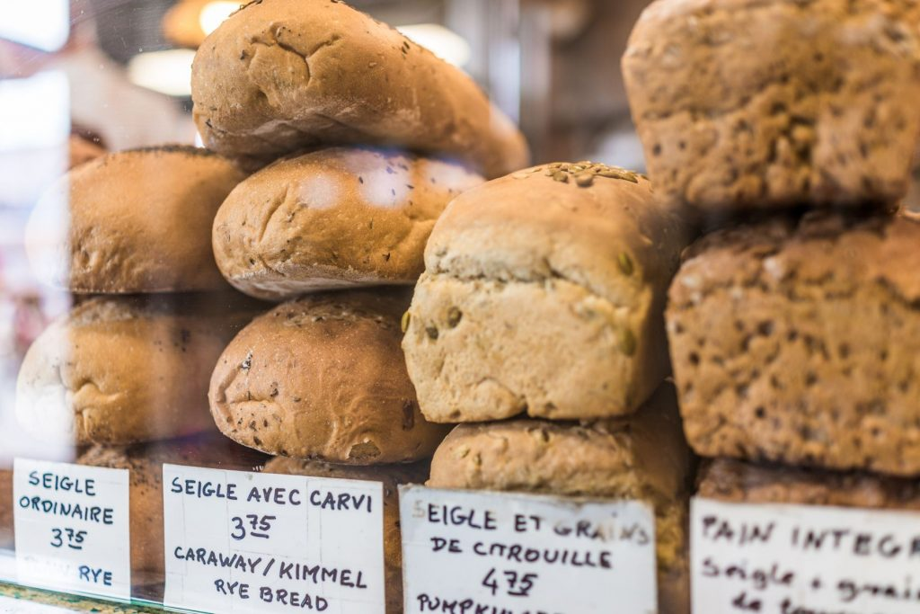 Rye bread display with signs in French at bakery behind window