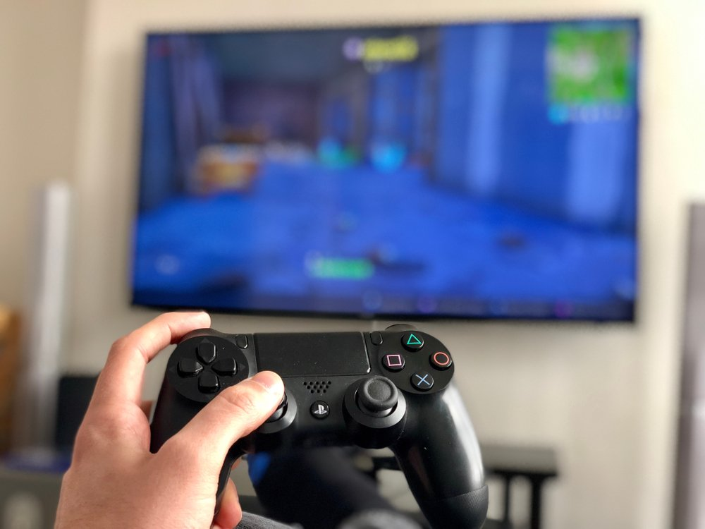 A man holds a Sony PlayStation 4 controller while playing a console video game on a television