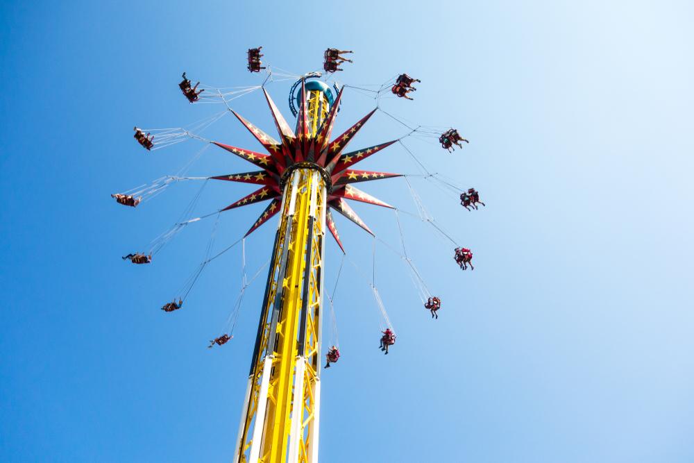 People ride a roller coaster ride at a carnival amusement park ride in San Antonio
