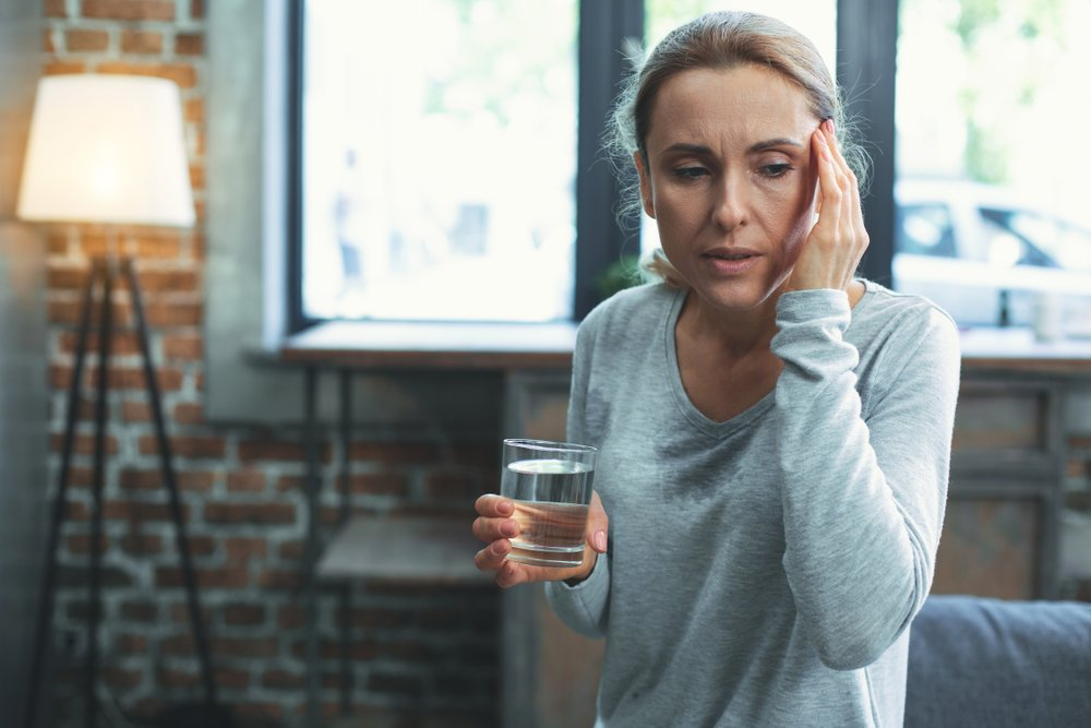 woman holding glass of water looks dizzy