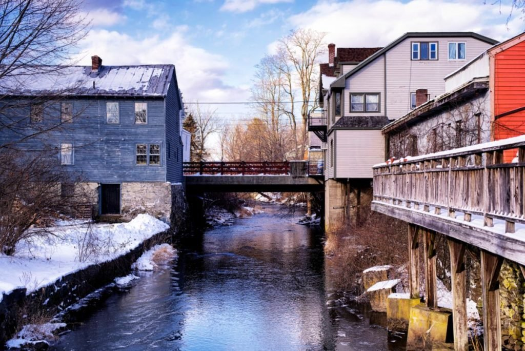 Old buildings lining the williams river running through the village of west stockbridge massachusetts on a sunny winter day.