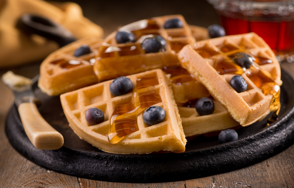 Delicious fresh homemade blueberry waffles with fresh blueberries and maple syrup