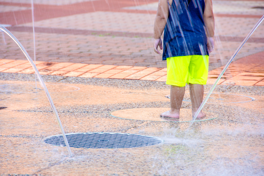 young child playing in city water splash pad