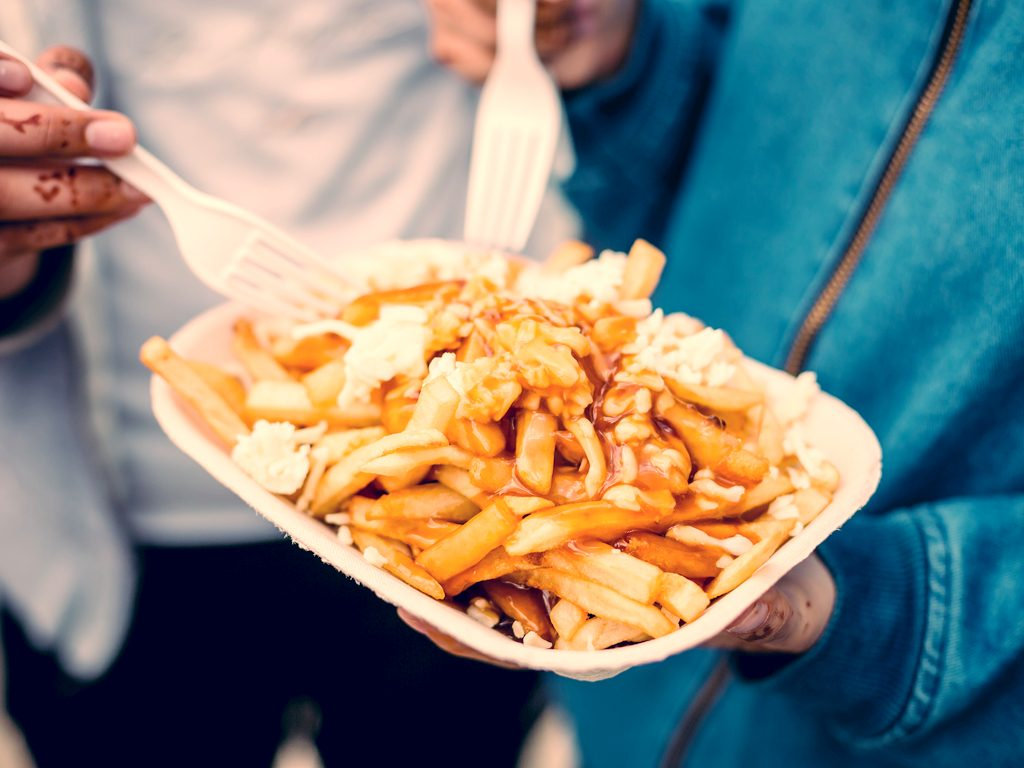 Poutine being eaten with forks