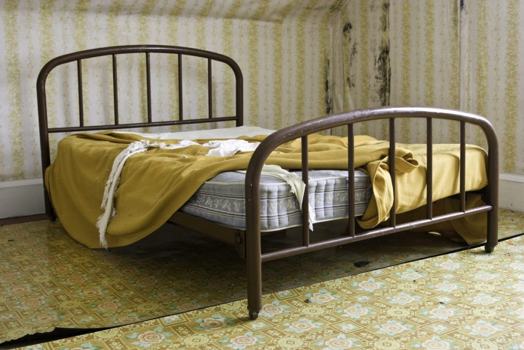 Old bed with no sheets