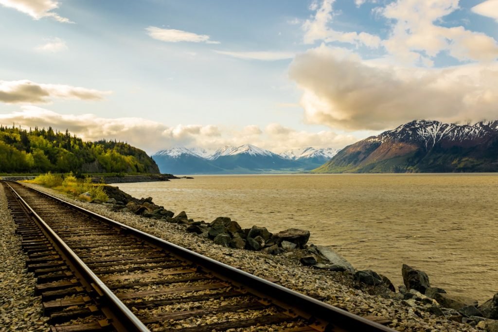 Part of Alaska railroad in the Chugach National Forest with mountain range and Turnagain arm in background.