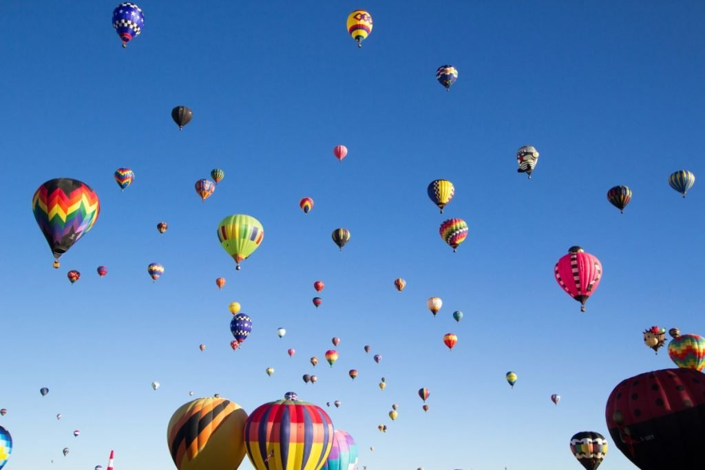Various photos of hot air balloons in the air or launching at the 2017 Albuquerque Balloon Fiesta.