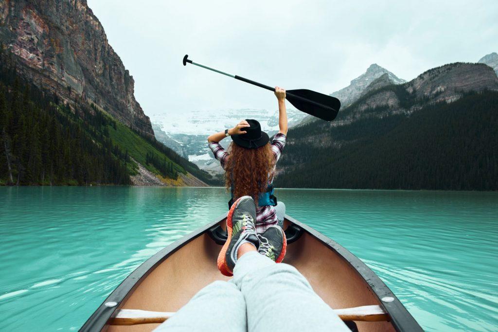 Shoot of young woman traveller on canoe enjoying nature views