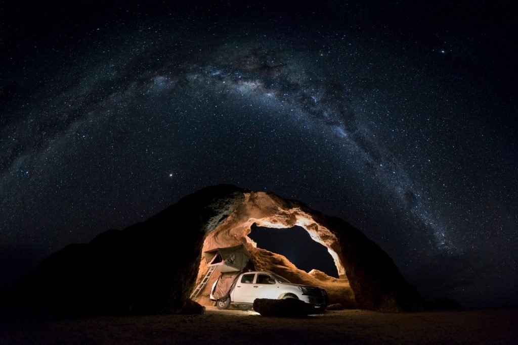 Spitzkoppe. Rock arch with 4x4 under it and milky way above