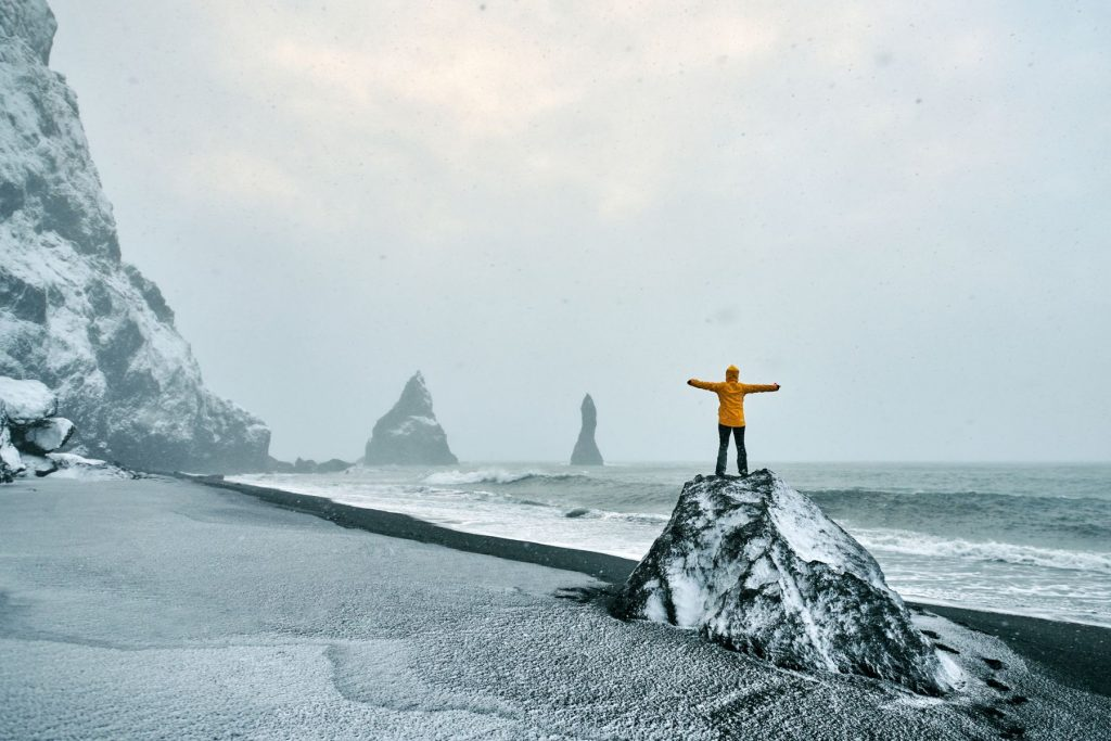 rear view of hiker woman on rock on Reynisdrangar beach in Iceland enjoying freedom.