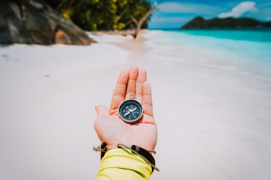 La Digue Island. Hand with compass against tropical sandy beach and ocean