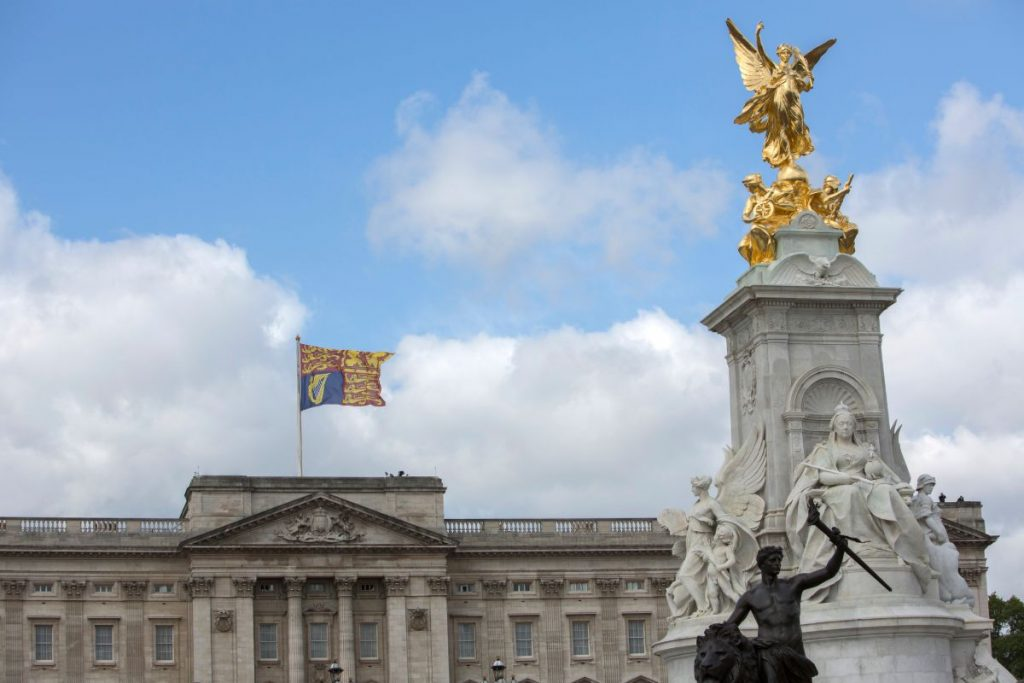 """Queen Victoria Statue and the Royal Standard flag flying above Buckingham Palace, London, England"""