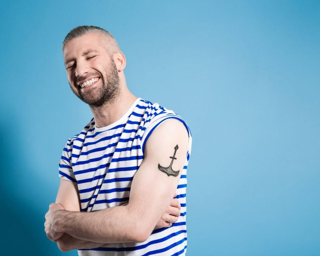Portrait of happy bearded sailor man with anchor tatoo on shoulder wearing white and blue striped clothing. Standing with arms crossed against blue background and laughing with eyes closed.