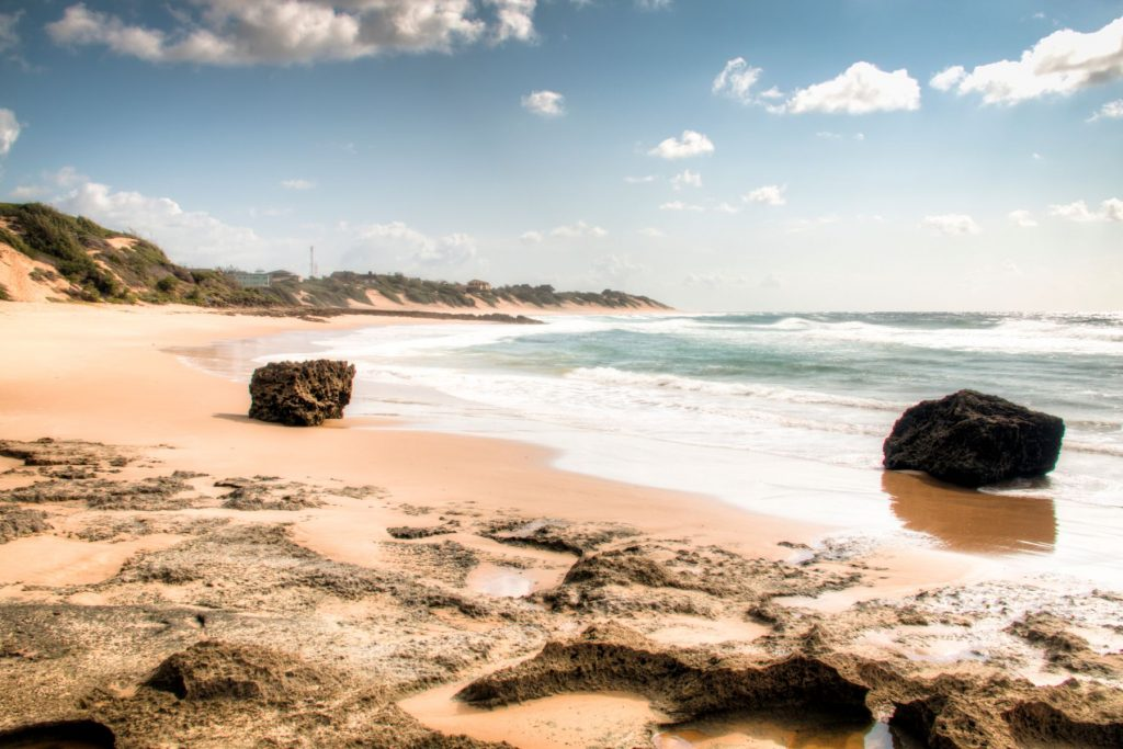 Very rustic and empty beach with large rocks at the Indian Ocean in the coastal town Praia do Tofo in Inhambane, Mozambique