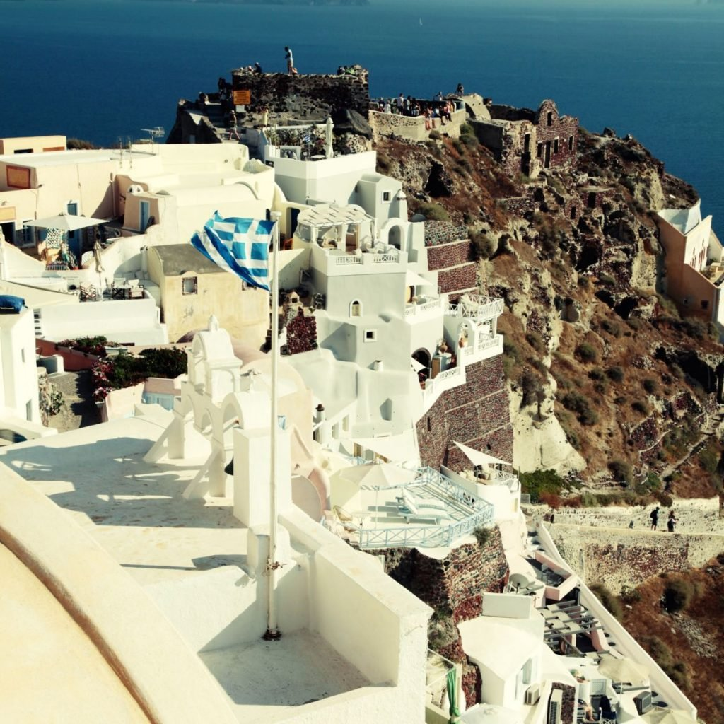 View of Oia town and old castle of Oia, Santorini, Greece. Square toned image