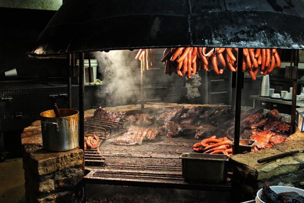 Sausages hanging over brisket smoking over a large BBQ pit.