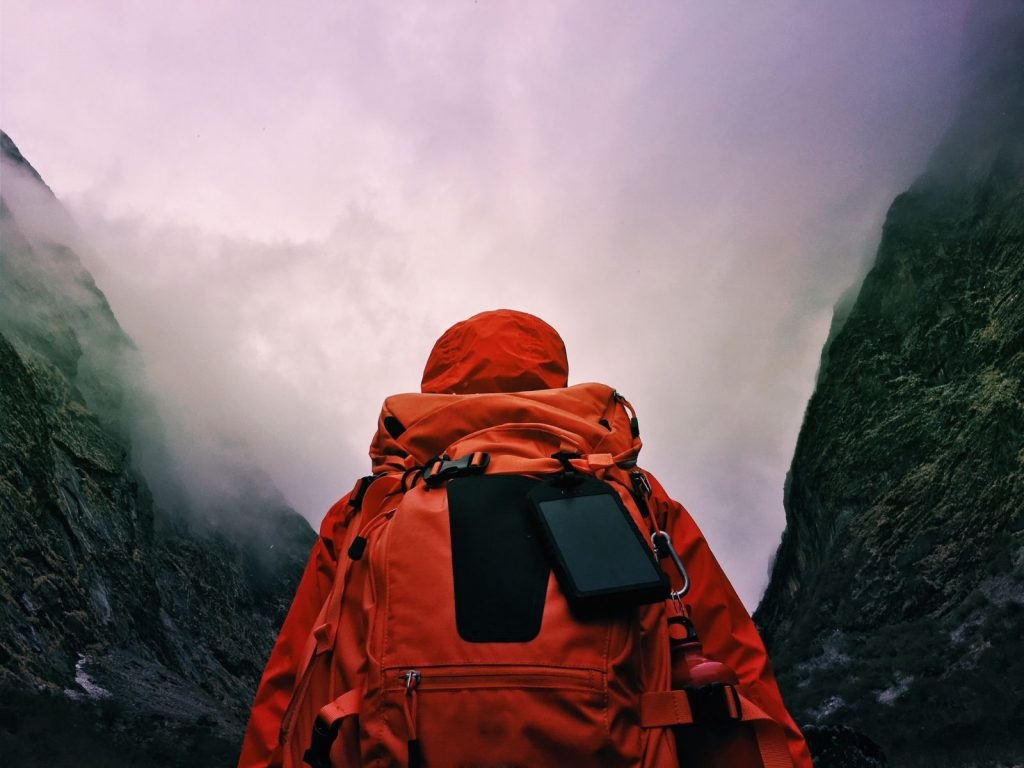 Photo of a hiker crossing the road fully equipped with a backpack
