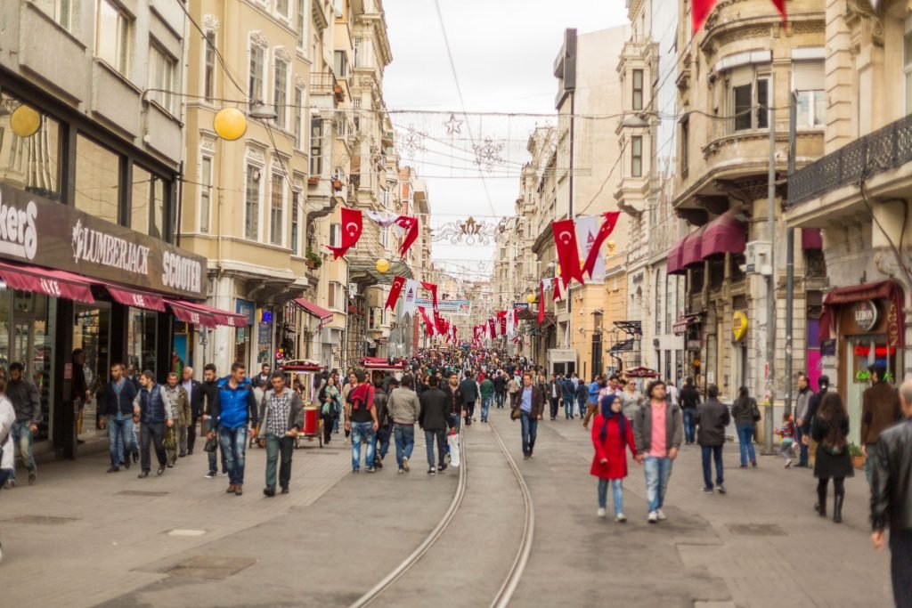 Crowds of tourists, shoppers and local people walk down Istiklal Avenue in the Beyoglu area of Istanbul decorated with flags commemorating October 29 the Turkish Republic Day public holiday