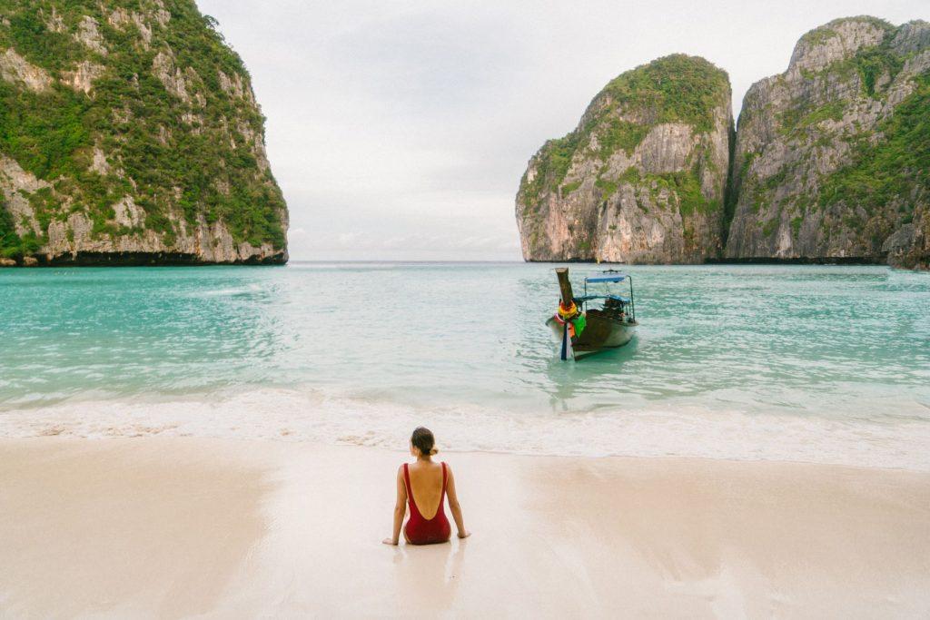 Young Caucasian woman sitting on Maya Bay beach in Krabi, Thailand