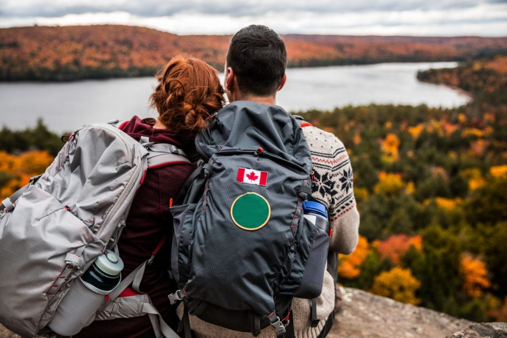 Young couple hiking in mountain and relaxing looking at view in the Algonquin Park, Ontario - Canada.