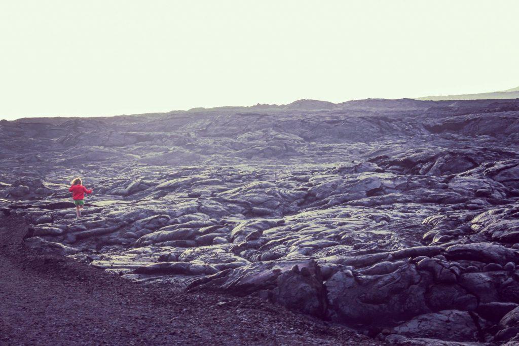 Barren land in Volcanoes national park, lava field, child explores the landscape