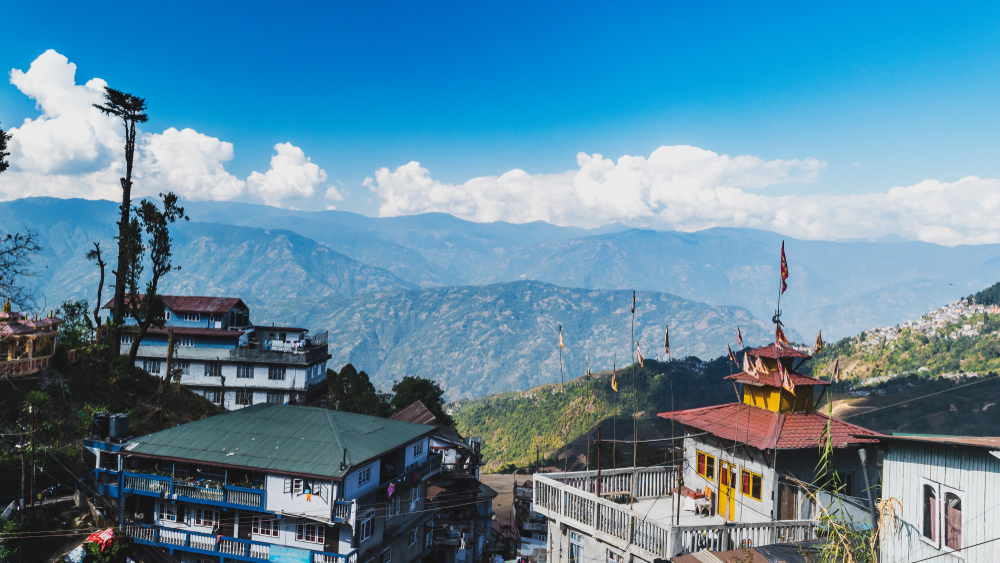 A hilltop view of house' roof with mountains and blue sky with clouds from Darjeeling Himalayan railway station on a misty morning
