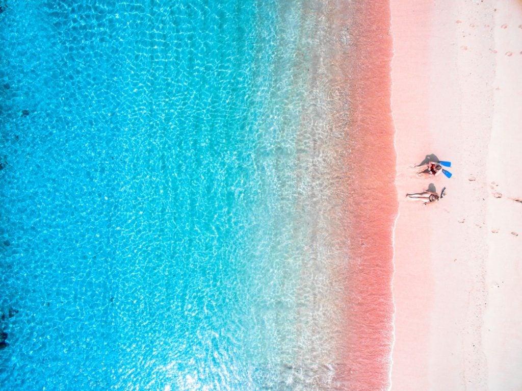 tourist Couple enjoys the Pink Beach Indonesia