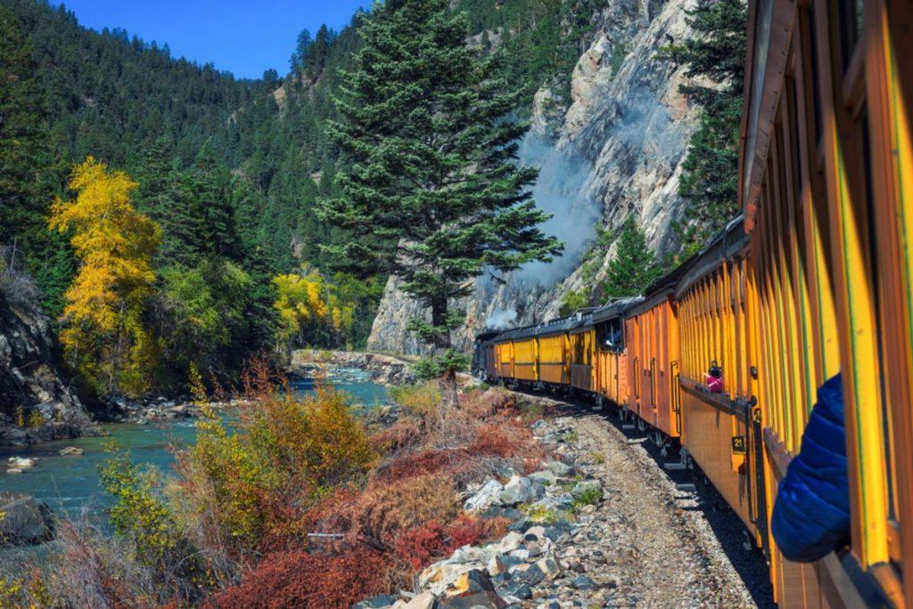 Historic steam engine train travels from Durango to Silverton through the San Juan Mountains along the Animas River in Colorado, USA