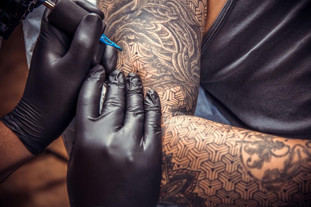 Master working tattooing in tattoo studio./Professional tattooist works in studio