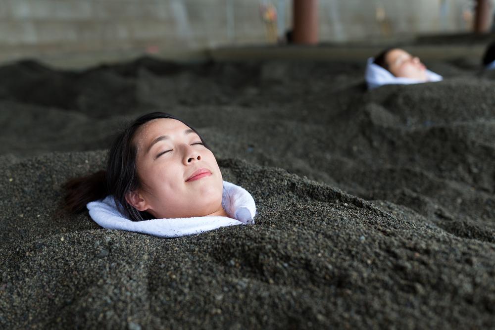 Woman enjoys a hot sand bath