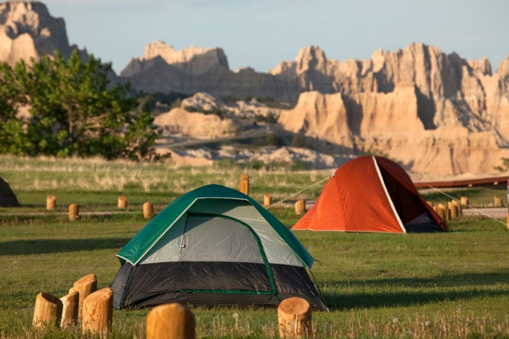 Tents stand in the Cedar Pass Campground with the eroded landscape of South Dakota's Badlands National Park in the background.