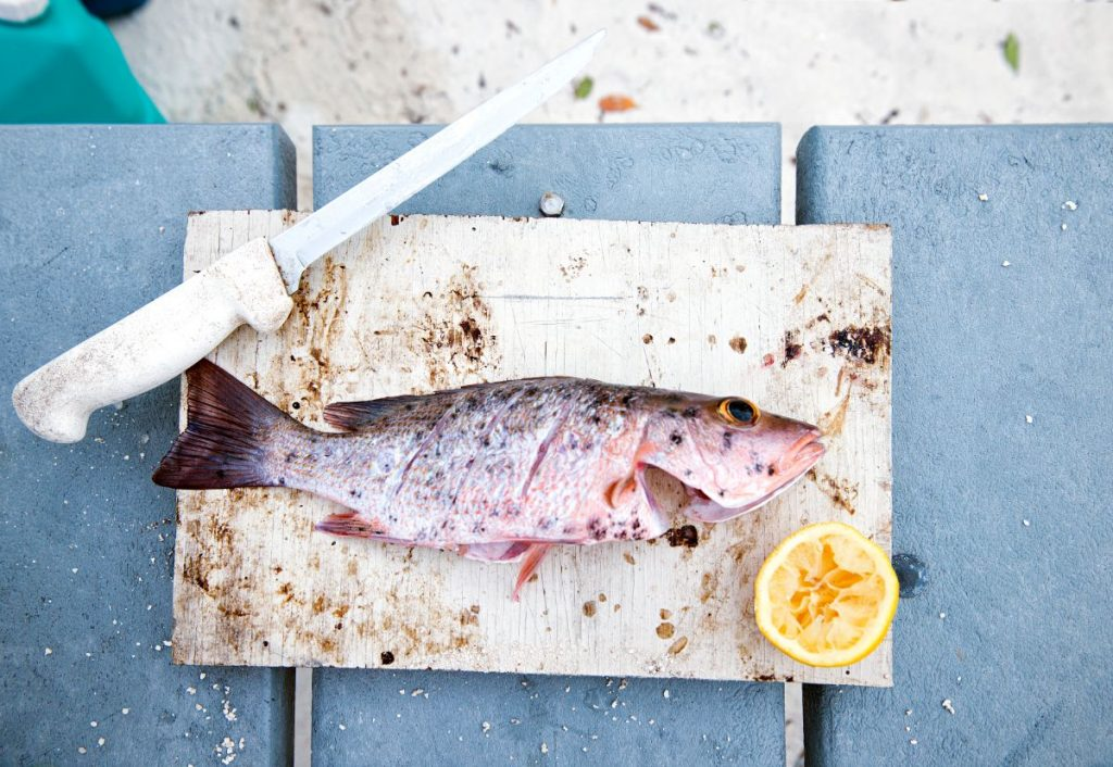 a freshly caught red snapper that has been sliced and doused in lemon juice. It sits on a cutting board waiting to be cooked.