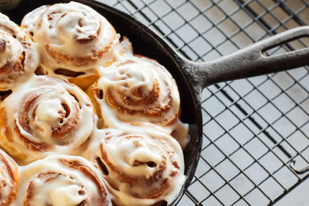 Homemade cinnamon rolls or buns baked in a cast iron skillet and covered with cream cheese icing.