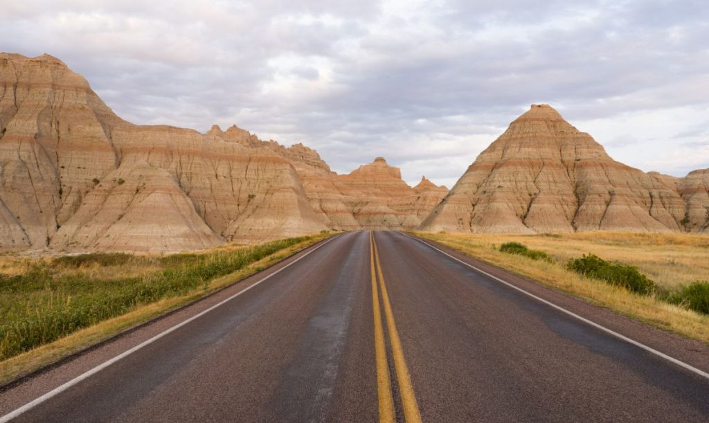 The road leads through rock formations in the South Dakota Badlands
