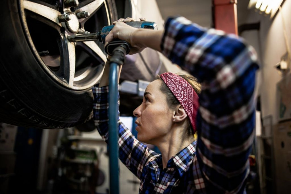 Female mechanic working on car tire service