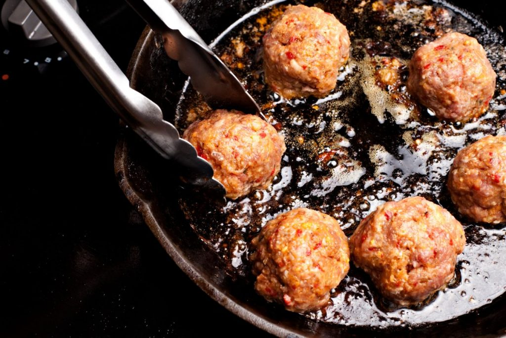 Tongs turning meatball in frying pan