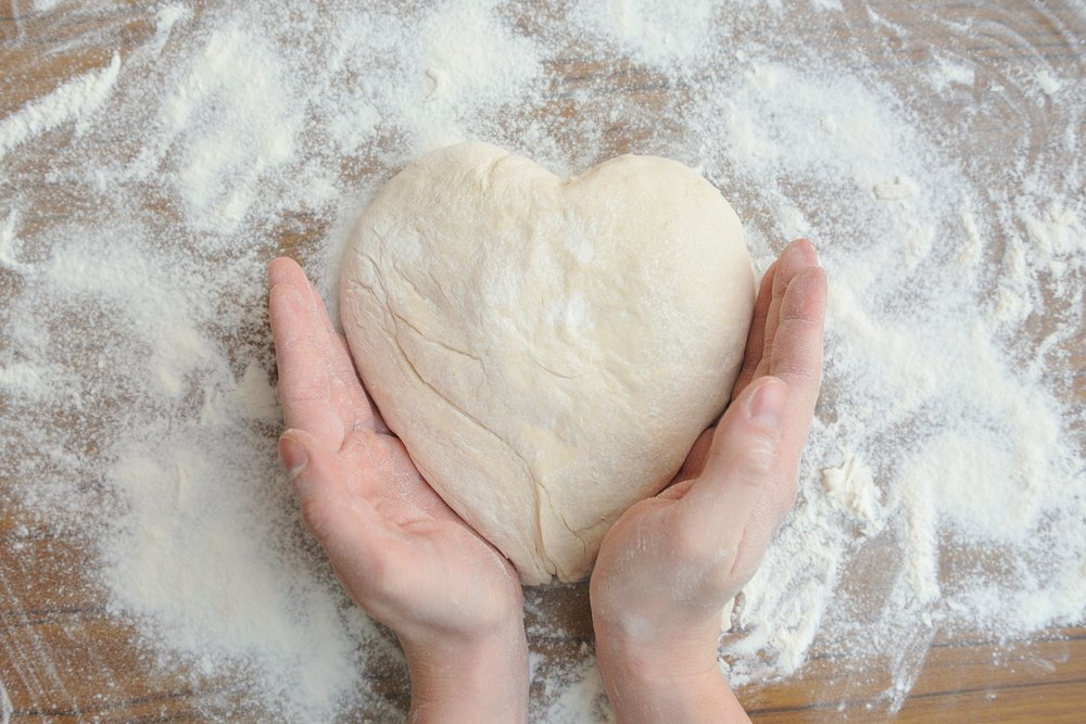 Raw dough in the shape of a heart and a touch of hands to it.