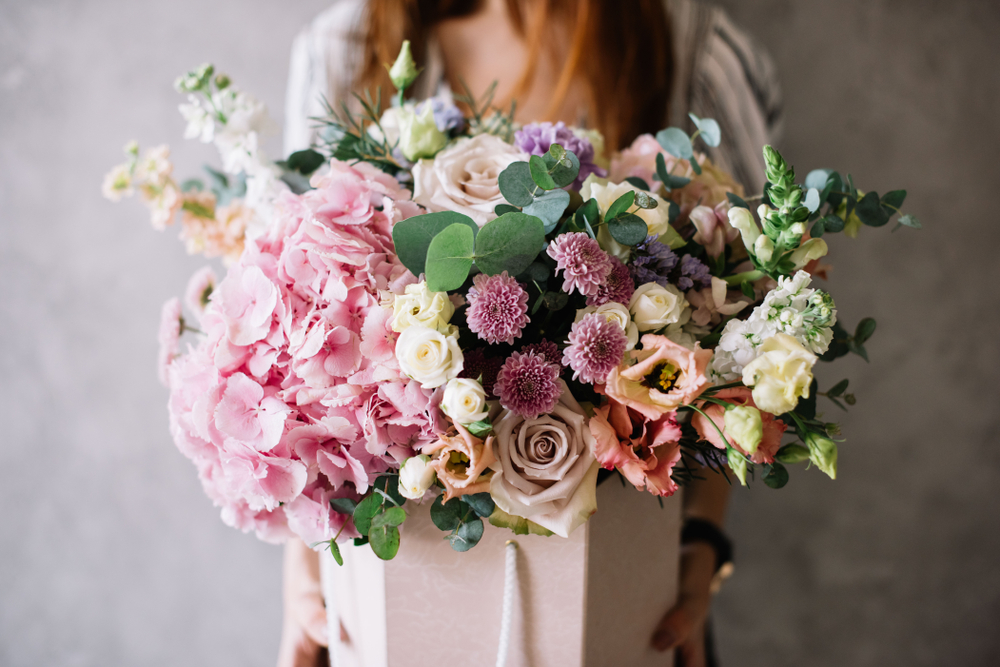 Very nice young woman holding beautiful tender blossoming bouquet of fresh hydrangea