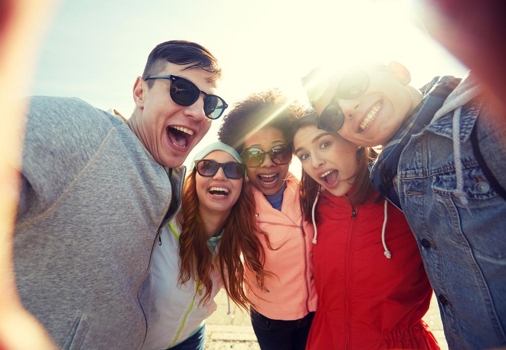 group of happy laughing teenage friends taking selfie outdoors