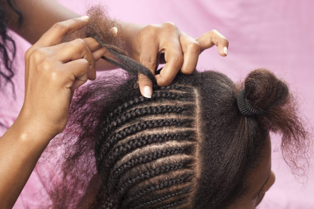 black woman doing cornrows