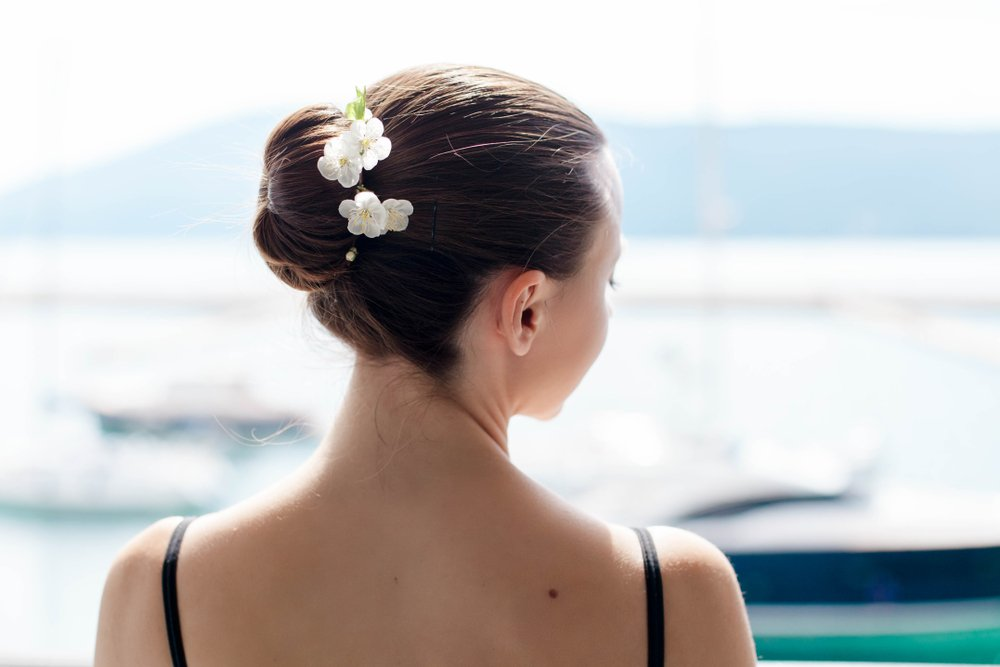 Ballerina stands back and has hair bun with spring flowers.