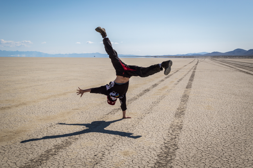 A young man does a cartwheel on the playa of the Black Rock Desert