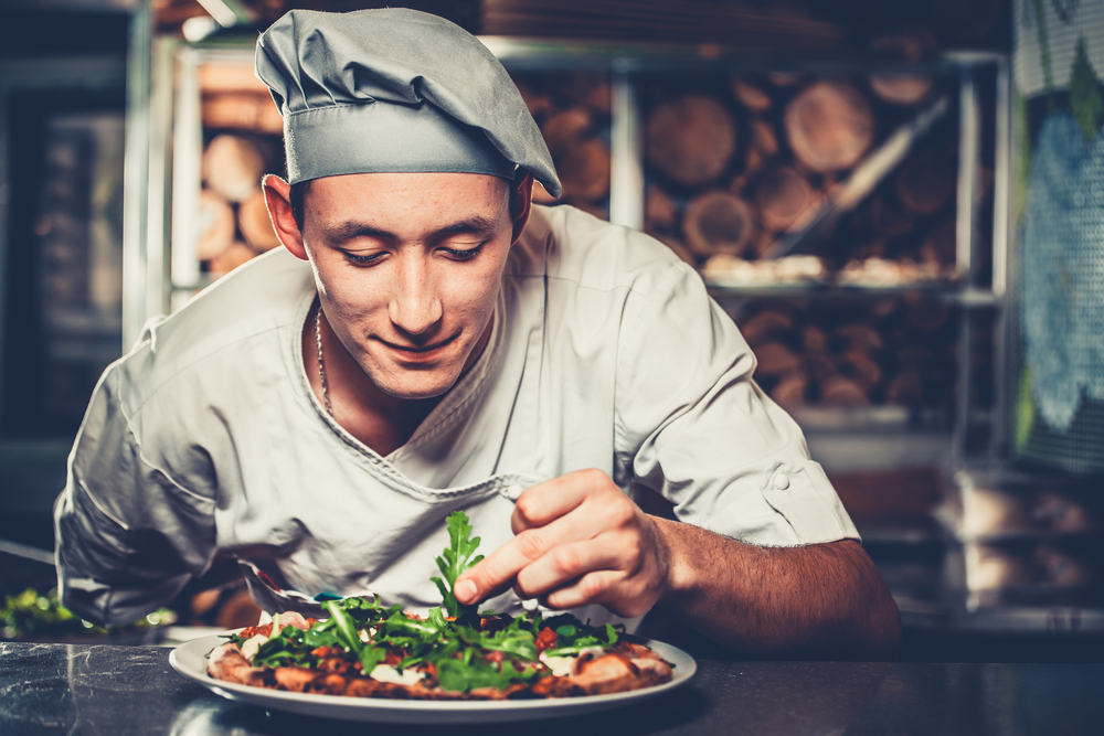 Young smiling chef in white uniform and gray hat decorate ready dish with green rucola herbs in interior of modern restaurant kitchen.